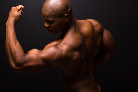 strong african american bodybuilder posing on black background photo