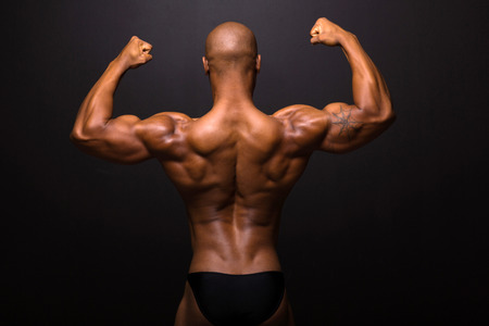 rear view of afro american male bodybuilder posing on black background photo