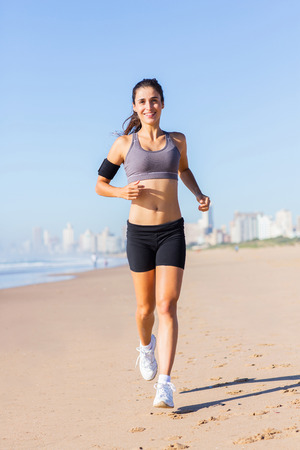 healthy young woman running on beach in the morning photo