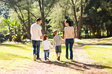 rear view of young family walking in forest