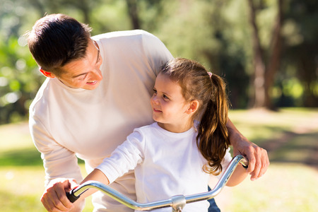 father teaching daughter: happy young father riding bicycle with his daughter outdoors