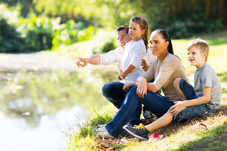 children pond: young family of four sitting by lake