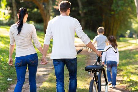 野外を歩いている若い家族の背面図