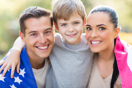 lovely american family with US flag outdoors on 4th of July photo