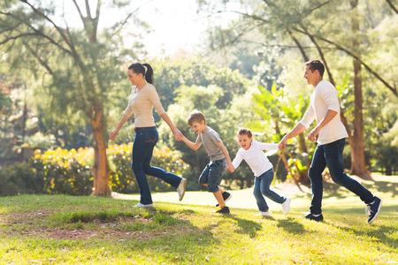 niños jugando en el parque: parte de la familia lúdica en la mano corriendo en el bosque