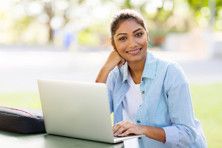pretty indian university student using laptop computer outdoors photo