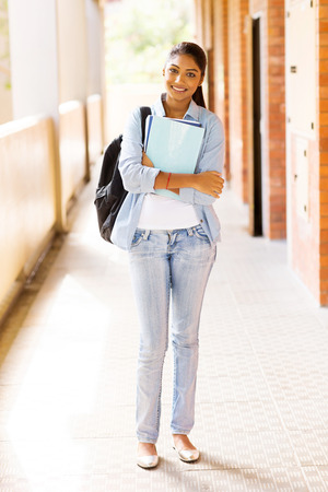 uni: beautiful indian college girl holding books standing by passage