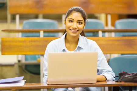 pretty female indian college student using a laptop in lecture room photo