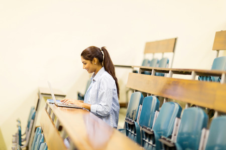 girl notebook: indian college student using laptop computer in lecture hall