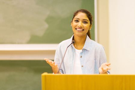 pretty indian female college student giving a speech in lecture hall