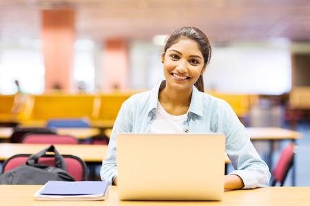 Jovencita hermosa usando la computadora portátil en la sala de conferencias Foto de archivo - 28971402
