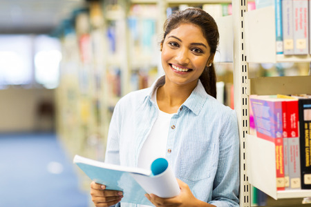 indian student: pretty indian college girl reading a book in library