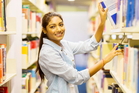 happy female indian college student pulling a book off shelf in library photo