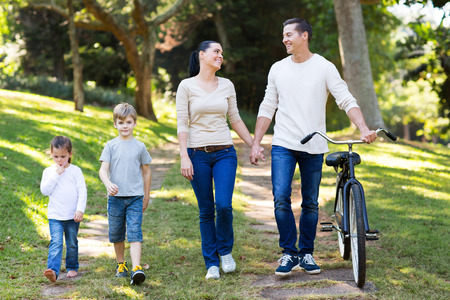 lovely young couple and kids walking outdoors in the park photo