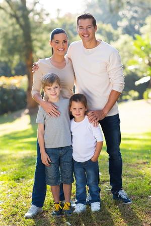 full length portrait: beautiful young family portrait outdoors in park