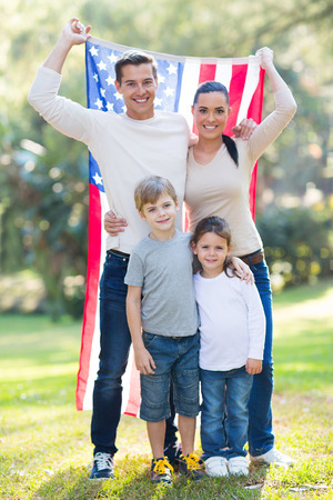 american family of four with USA flag outdoors photo