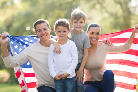 portrait of beautiful modern american family with USA flag outdoors