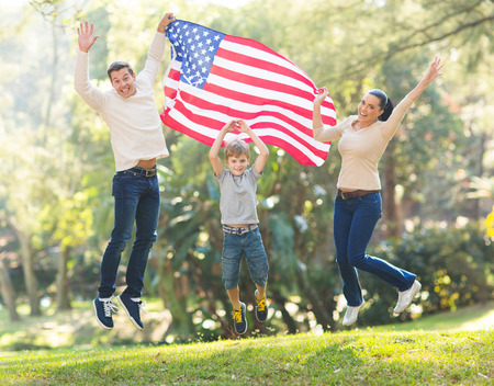 cheerful american family jumping with USA flag on 4th of july