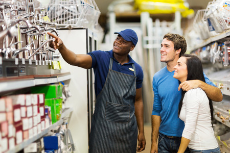 hardware store: friendly african hardware store assistant helping young couple choosing taps