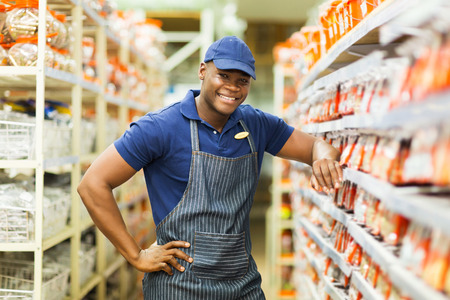 home improvement store: smiling african hardware store worker standing by the fasteners aisle
