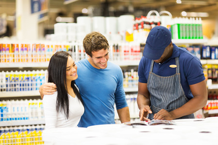 happy couple choosing paint color at hardware store with help of the shop assistant photo