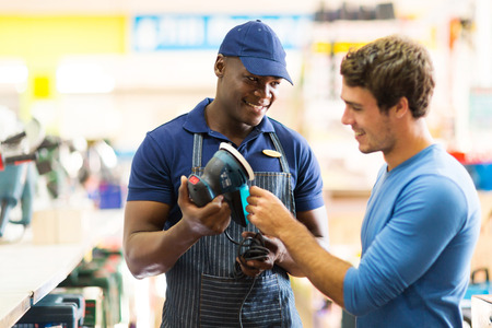 seller: friendly hardware store worker showing customer a sander