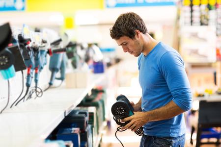 ハンサムな若い男研摩機ハードウェアの店でのショッピング