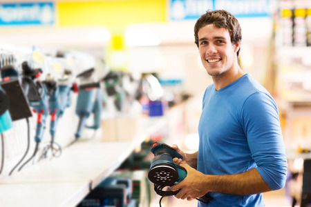 smiling young man purchasing a hand tool in hardware shop photo