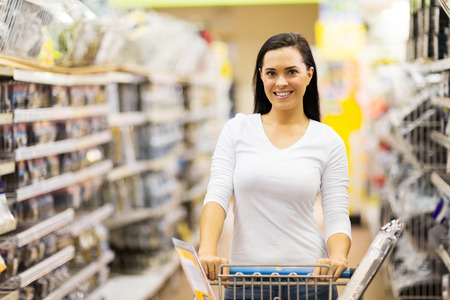 beautiful young woman pushing trolley in supermarket photo