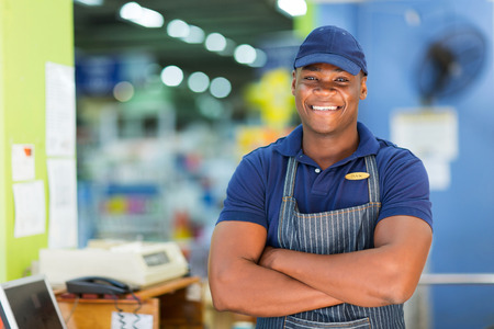 vendedor: apuesto cajera de supermercado africano de pie en la caja