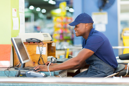 pos: happy african male cashier working at till point in supermarket Stock Photo
