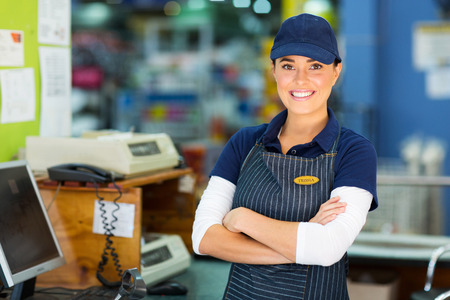 stores: gelukkig vrouwelijke ijzerhandel kassier met armen gevouwen
