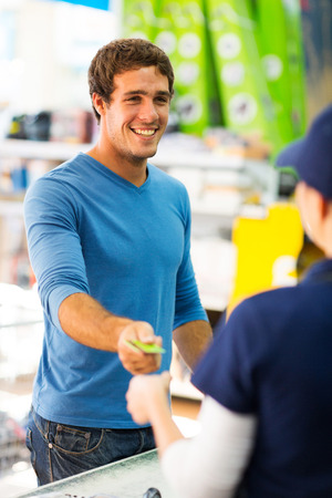checkout stand: happy young man handing over credit card to a female cashier at till point