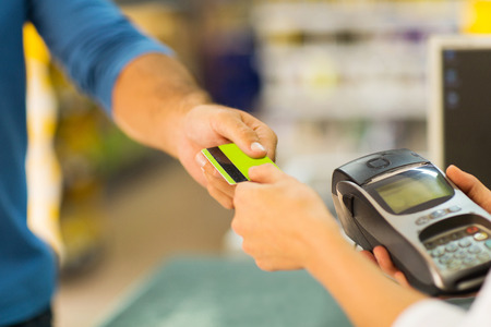 supermarket checkout: customer paying with credit card at supermarket