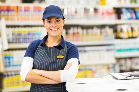 Piękna młoda pracownica supermarketu z rękami skrzyżowanymi