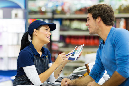 female paint store worker talking to customer over the counter photo