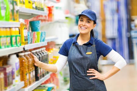 puesto de trabajo: hermosa vendedora supermercado pie en la tienda