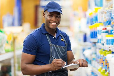 stores: gelukkig Afrikaanse winkelmedewerker controleren voorraad in de supermarkt Stockfoto
