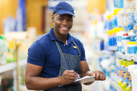 store clerk: happy african shop assistant checking stock in supermarket