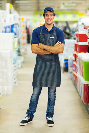 handsome supermarket worker with arms crossed Stock Photo