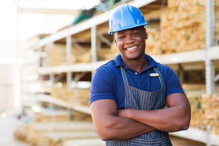 blue helmet: handsome african male warehouse worker with arms crossed