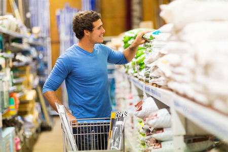 home improvement store: young man shopping for fertilizer in hardware store