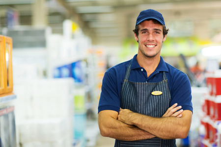 happy young salesman standing in hardware store photo