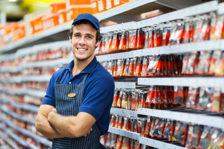 sales clerk: handsome hardware store salesman standing next to fasteners shelf Stock Photo