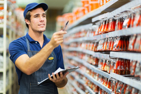 young man portrait: good looking hardware store worker counting stock Stock Photo