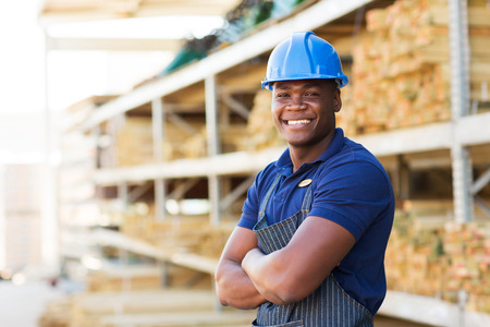 delantal: feliz trabajador industrial africano de pie en el almacén de material de construcción