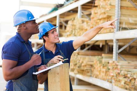 obreros trabajando: trabajadores de la tienda de hardware que trabajan en el departamento de la madera