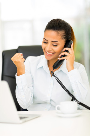 happy businesswoman receiving exciting news over the phone photo