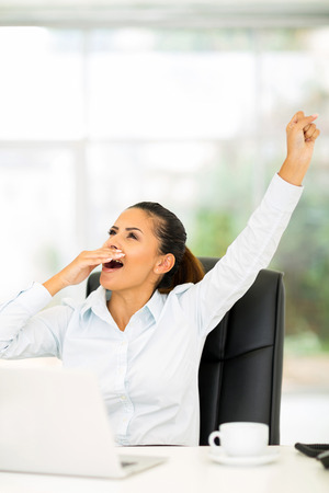 yawning: exhausted businesswoman yawning in office