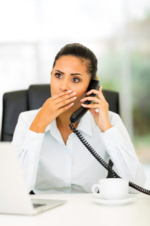 shocking: pretty young office worker receiving shocking news on the phone